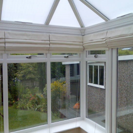 white roman blinds in a conservatory